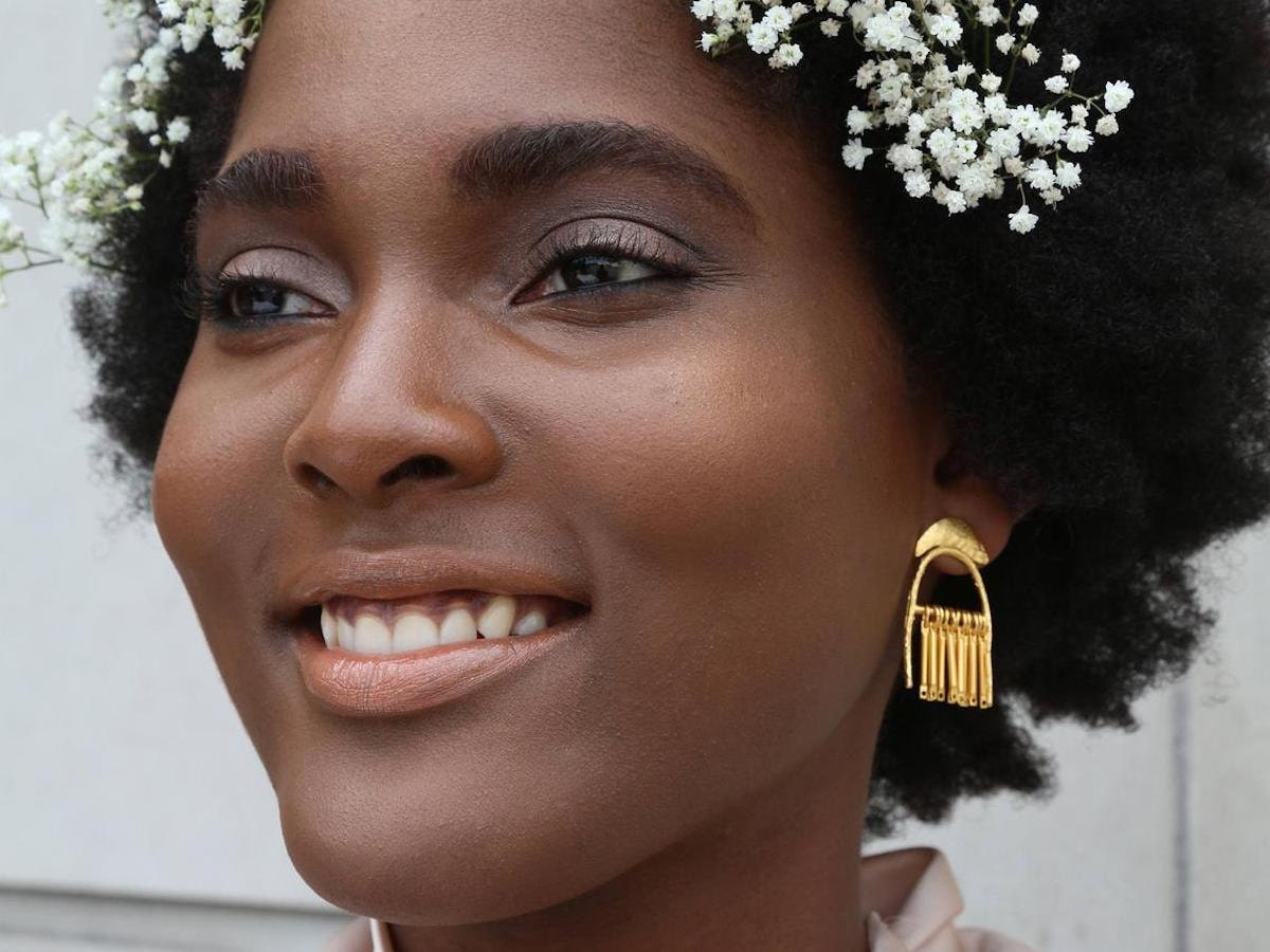 Woman modeling brass dangle statement earrings from Lingua Nigra