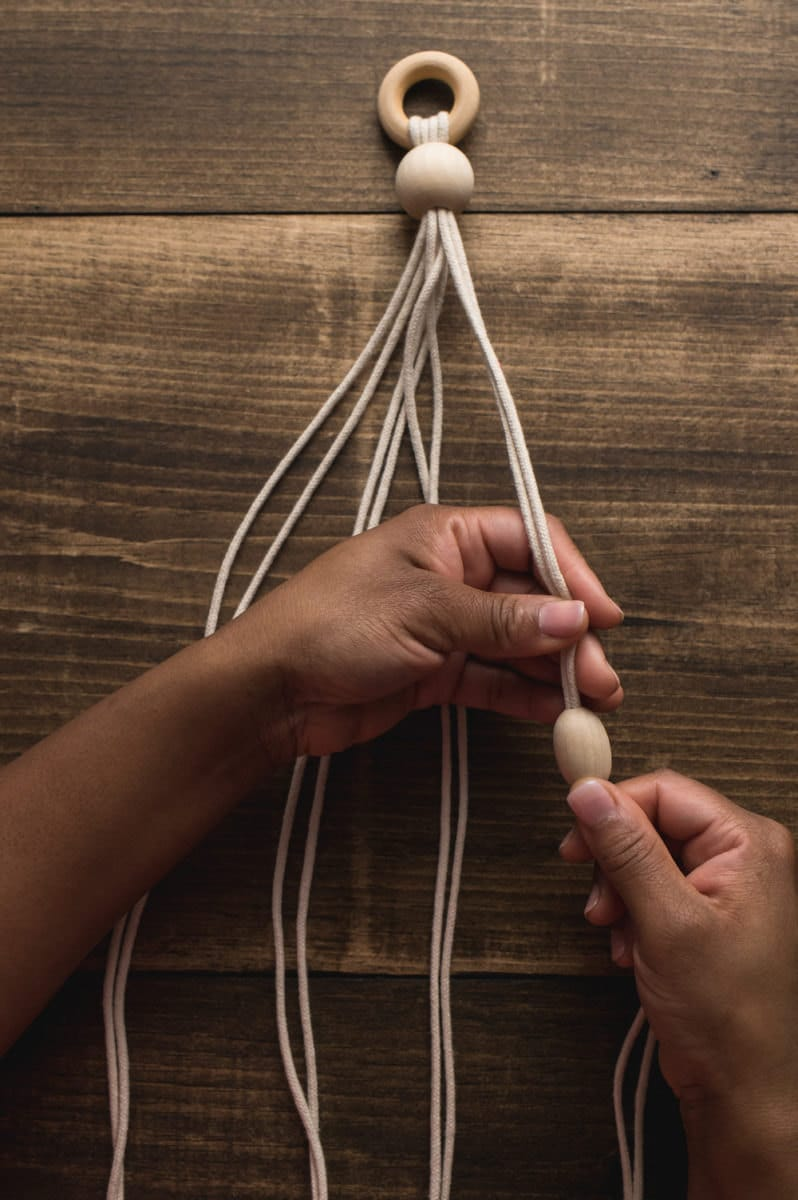 Hands separate the eight ropes into four groups of two and add a bead to each.
