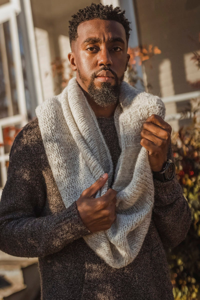 Nathan models a knit cowl—the pattern for which is available for instant download