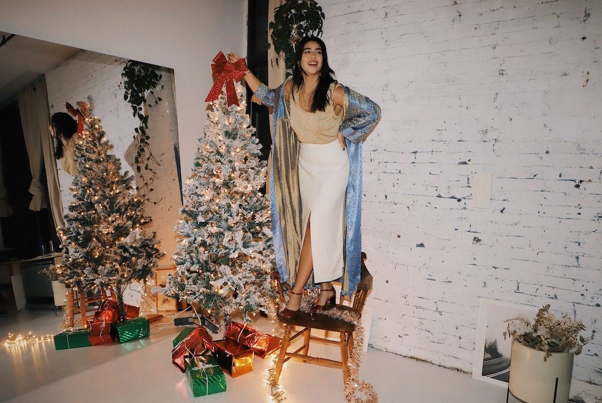 Tara Mazuki in her Brooklyn loft, wearing a festive holiday party outfit from Etsy as she decorates her Christmas tree