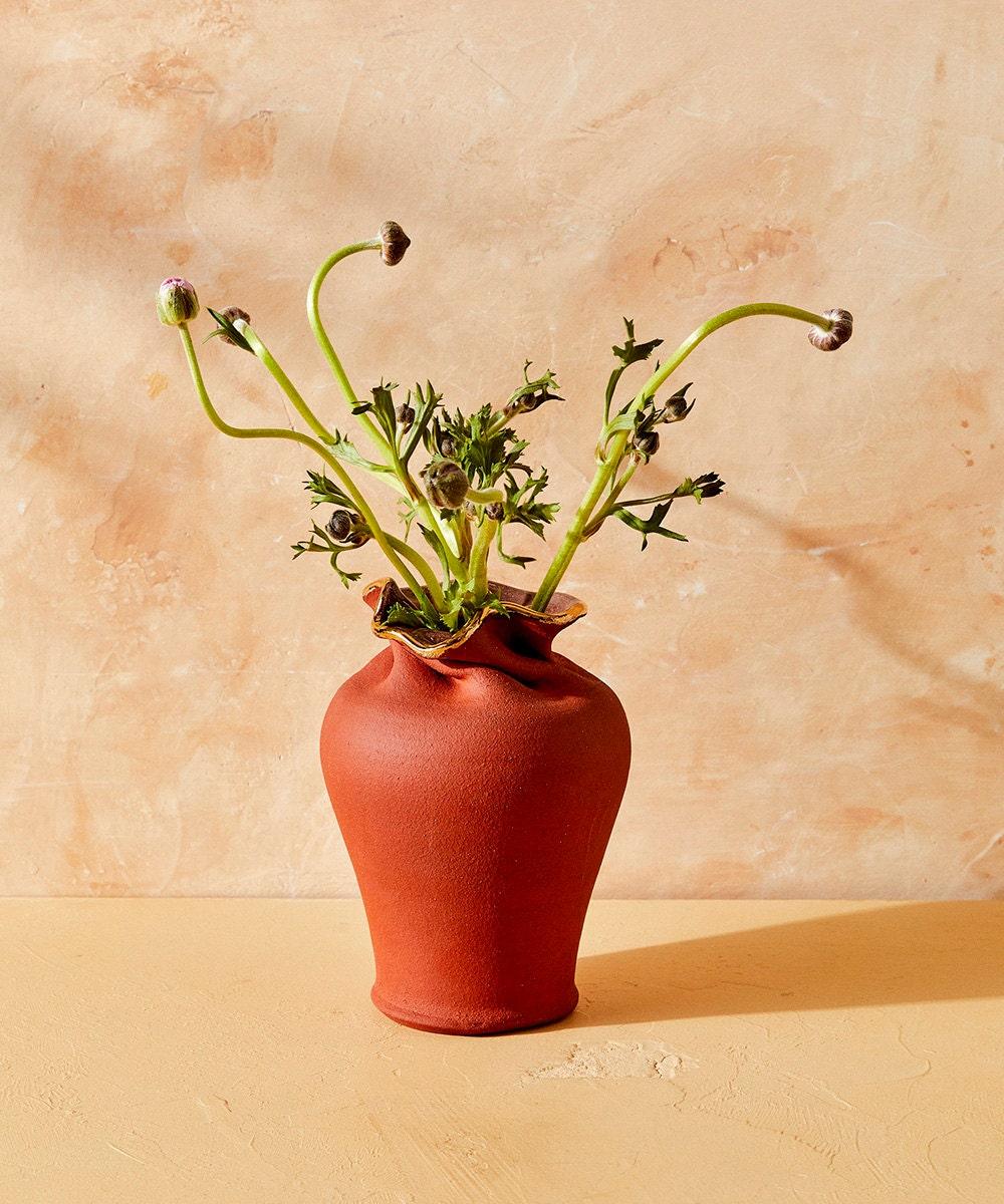 A ripple vase holds budding flowers.