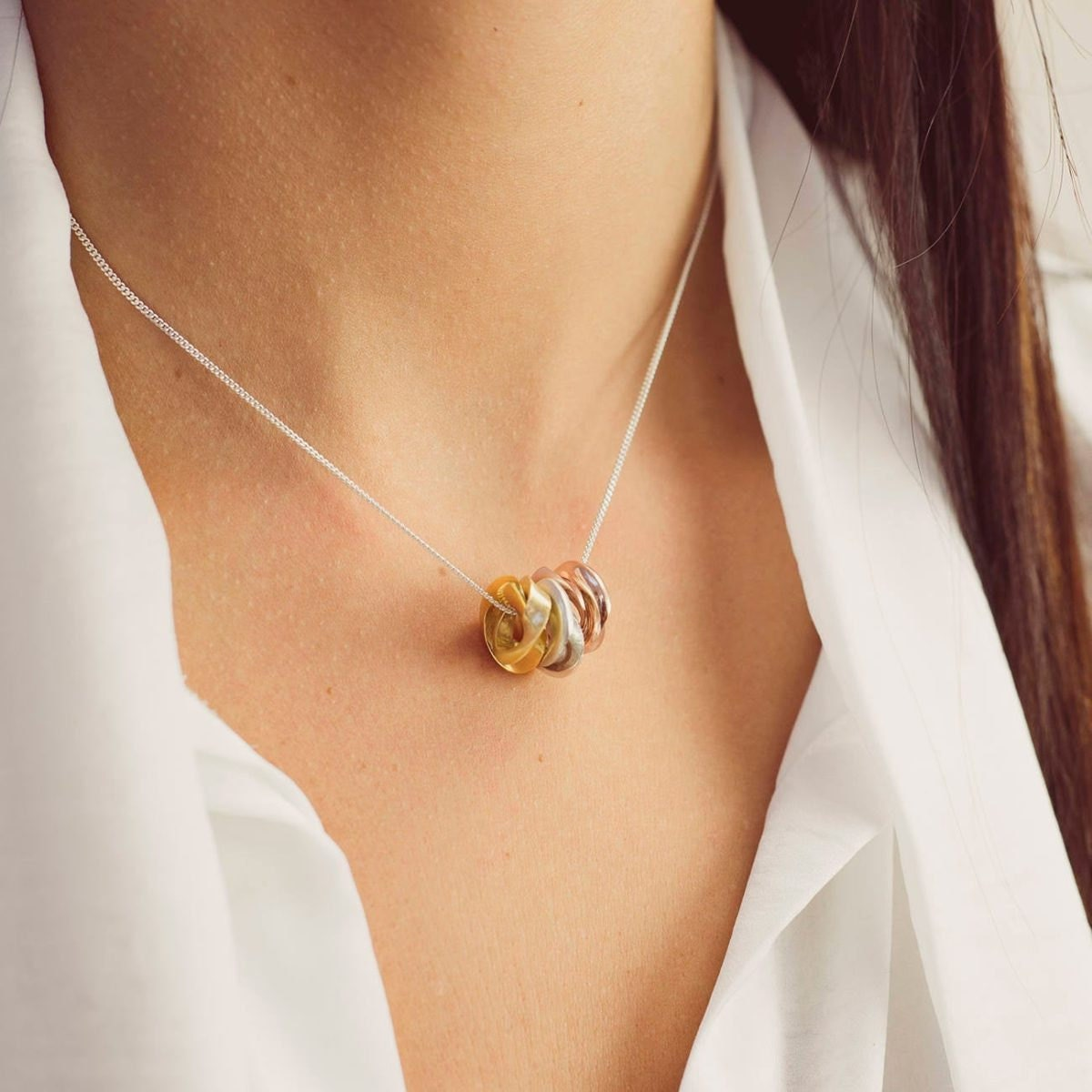 Personalized silver, yellow gold, and rose gold mobius necklace from Soremi Jewellery