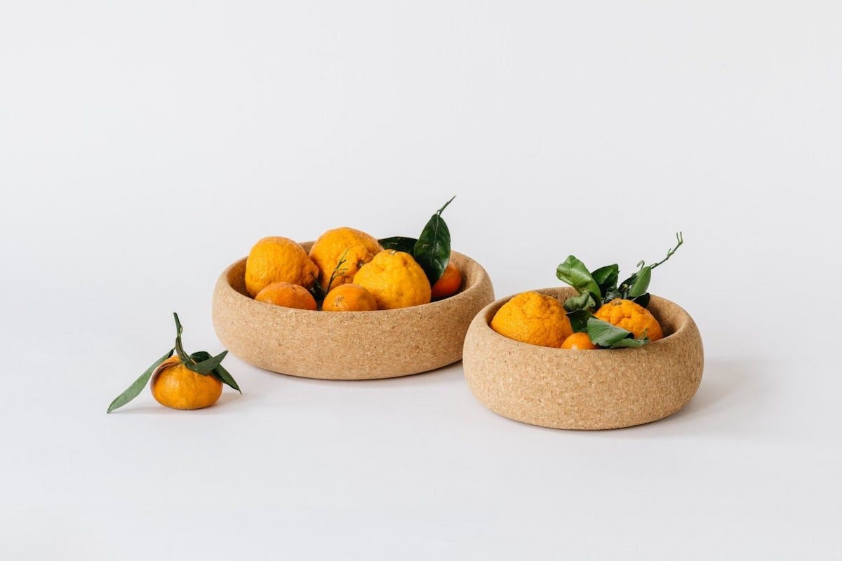 Two round cork bowls holding clementines