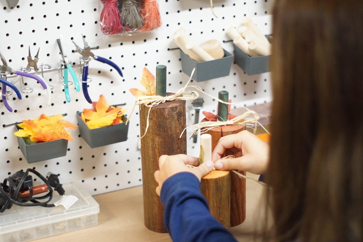 Sarah ties a piece of rafia onto a wooden pumpkin
