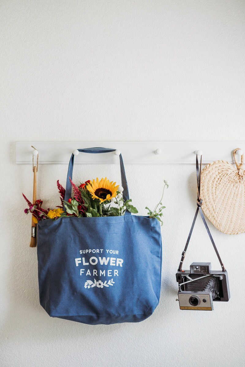 A reusable blue tote bag from Nature Supply Co. hangs on a peg board filled with flowers