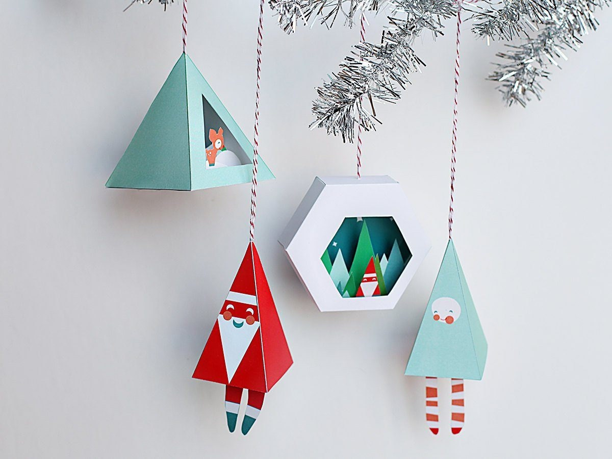 Set of four printable 3D Christmas ornaments hanging from a silver garland