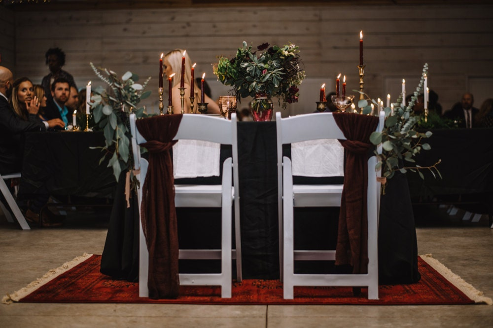 The couple's sweetheart table awaits them, adorned with gauzy fabric and bundles of eucalyptus