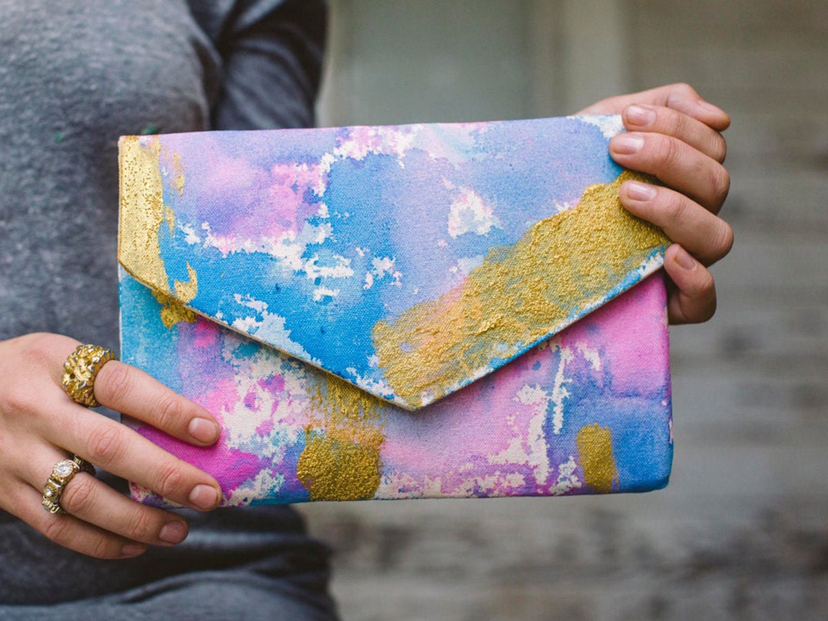 A pastel-colored clutch held by a model.