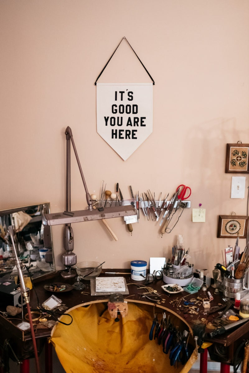 """Alicia's metal-smithing station, decorated with a pendant that reads """"It's Good You Are Here"""""""