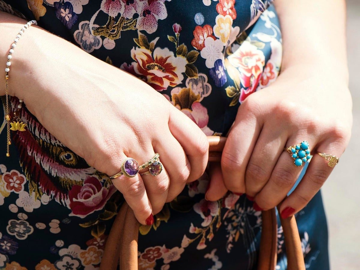 A woman holding a bag wears a colorful mix of vintage cocktail rings on her fingers