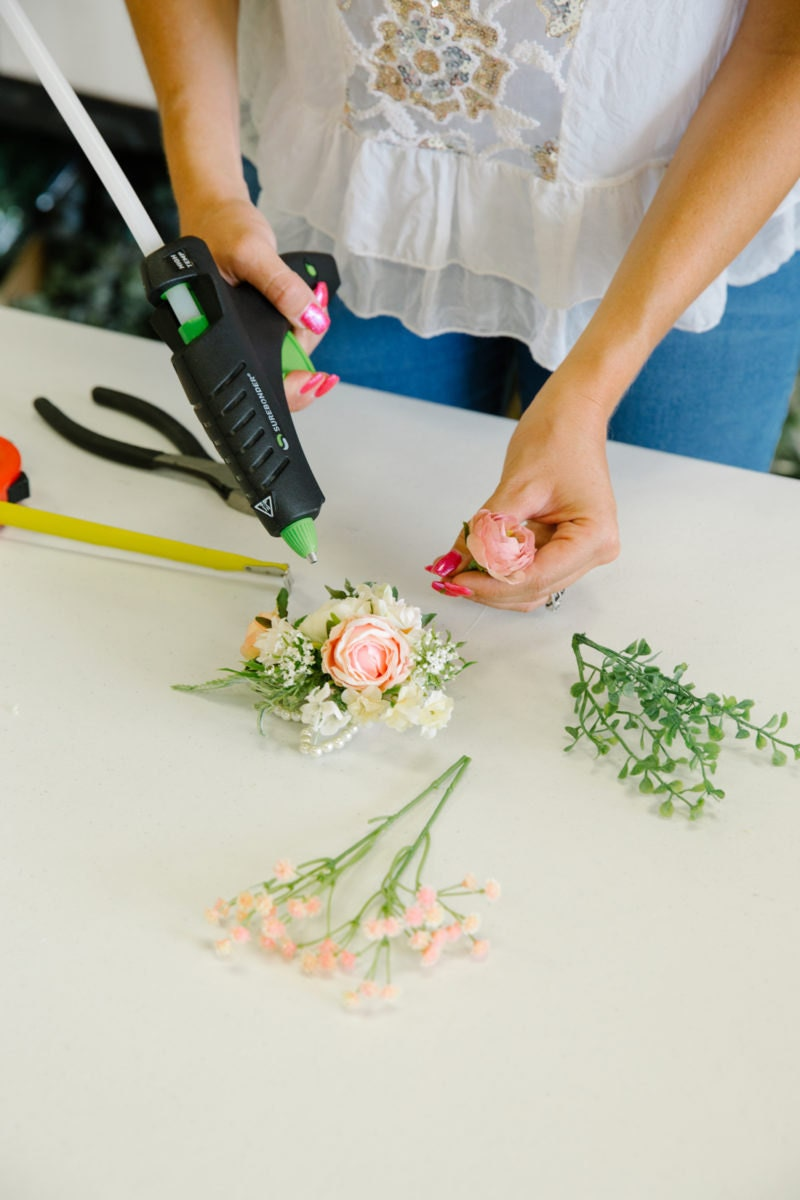 Brittany hot glues blooms in place to create an intricate floral arrangement