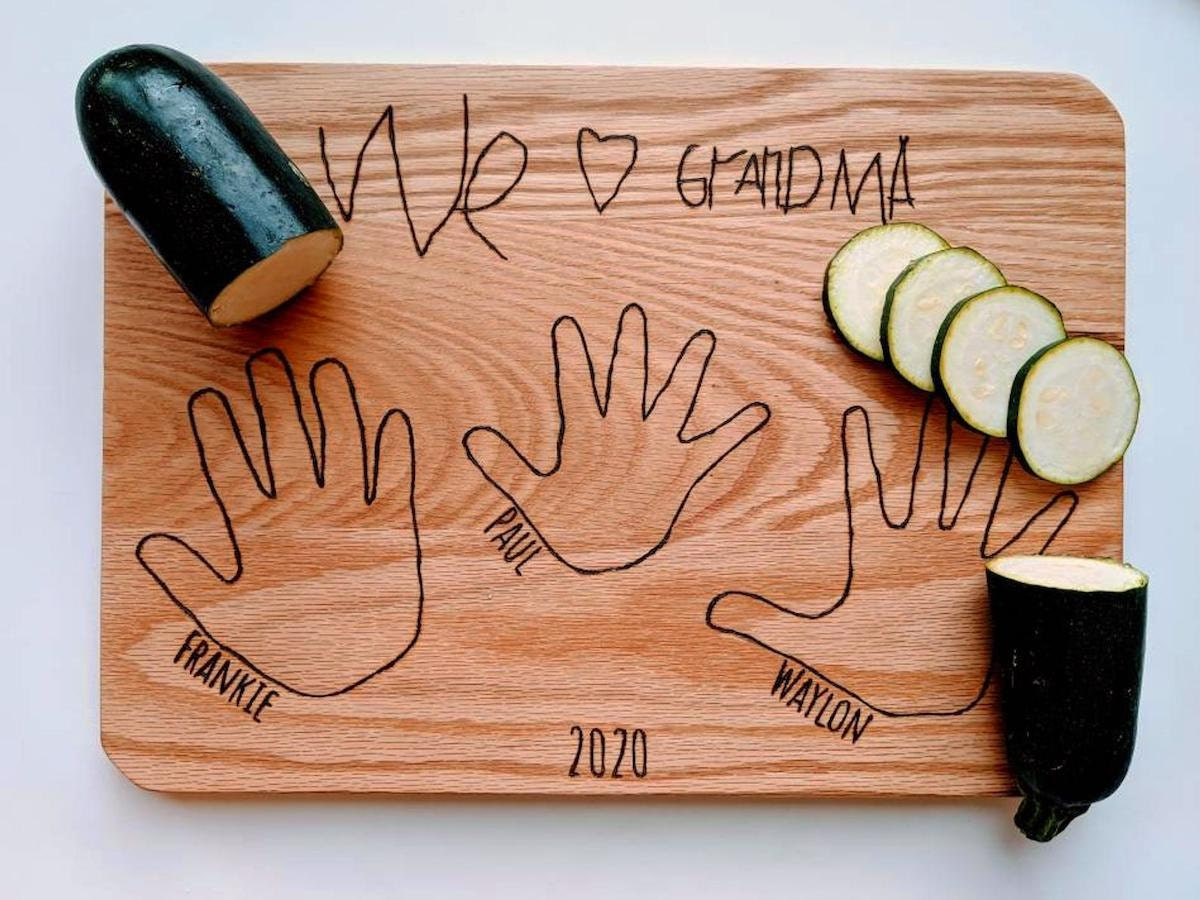A personalized cutting board engraved as a gift for grandma, with the outlines of the handprints of 3 grandchildren.