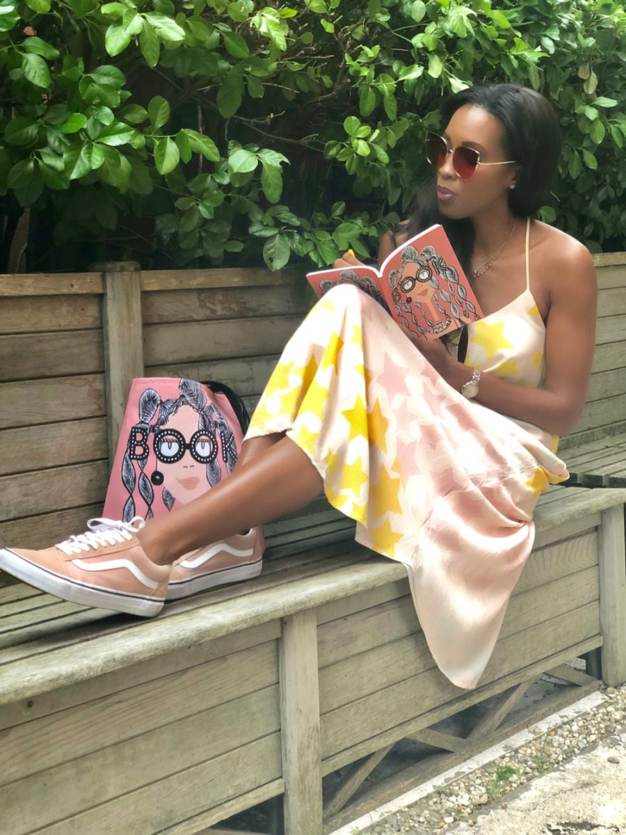 """A model posing with Karina's """"Book Smart"""" tote and notebook"""