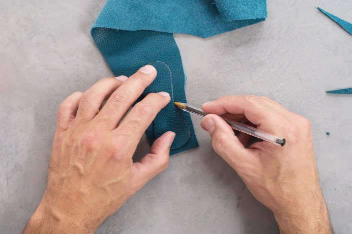 A pen traces the cut leather shape onto a second piece of leather
