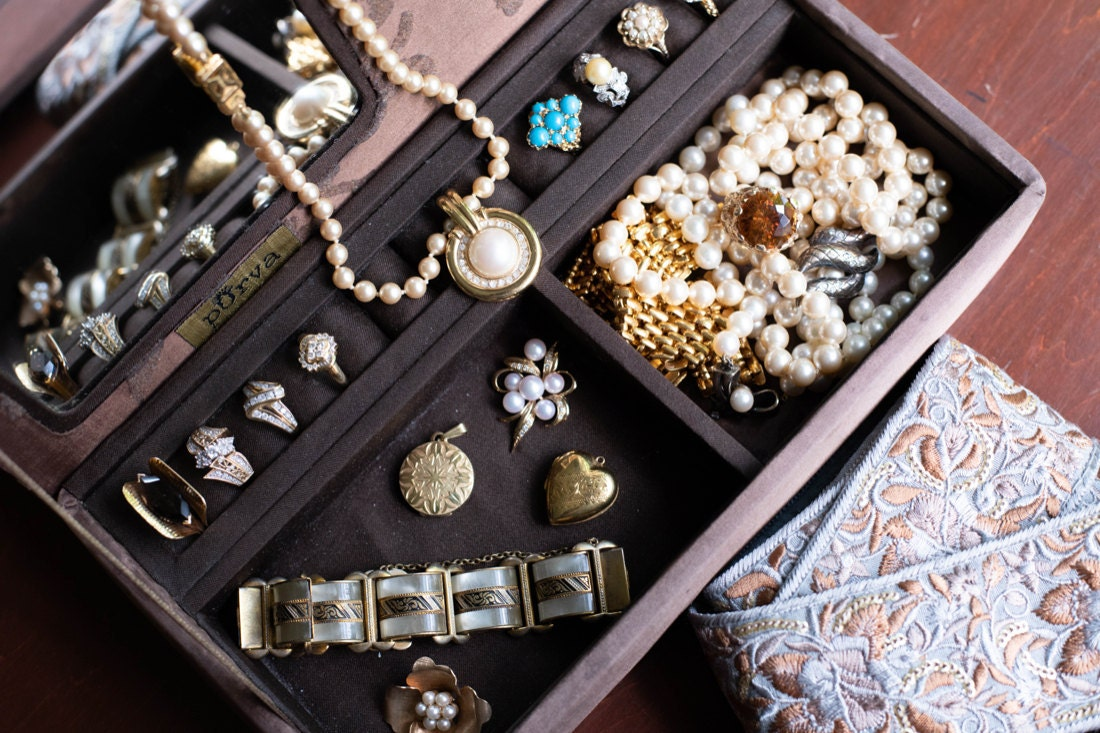 A jewelry tray filled with necklaces, lockets, and cocktail rings from KK Vintage Collection