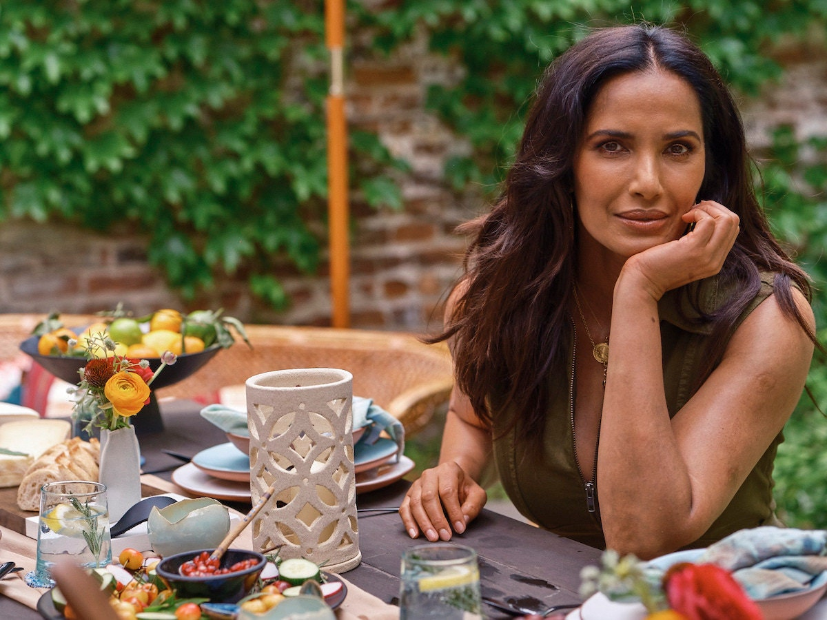 Padma Lakshmi sits at a set table