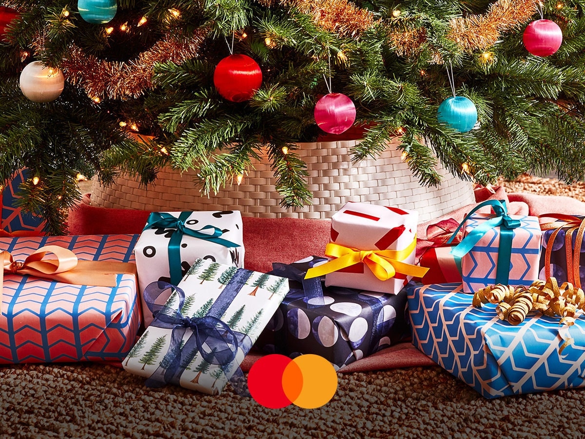 Colorful wrapped presents sitting under a Christmas tree