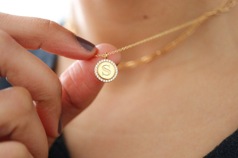 A personalized initial pendant necklace encircled in cubic zirconia stones, from EVREN.