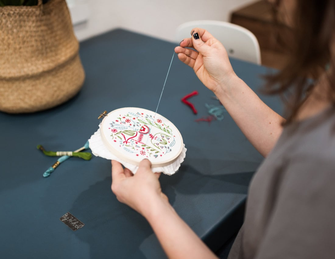 Liz stitches the details onto her Dala Horse design.