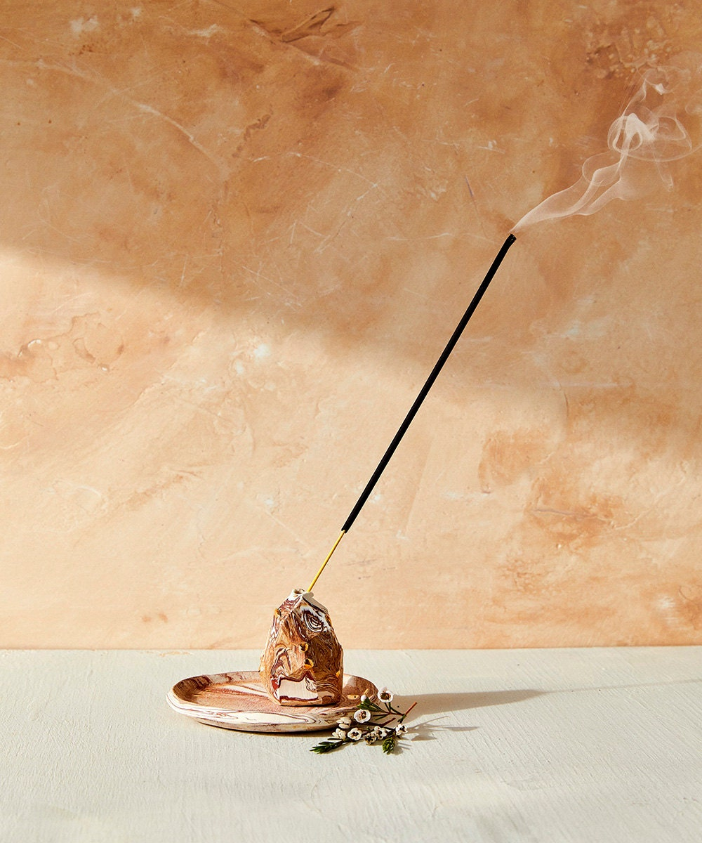 A stick of incense burns out of a marbled incense holder.