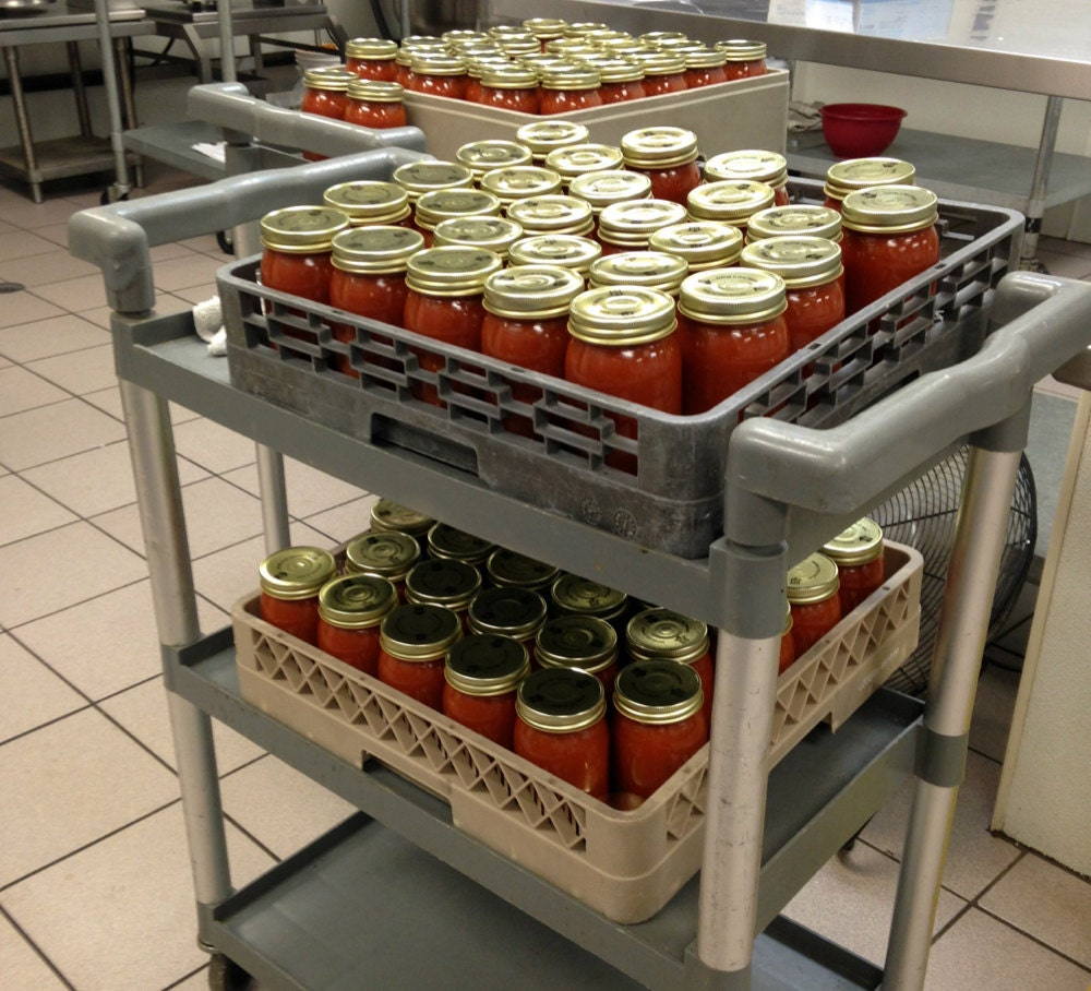 Stacks of jarred tomato sauce ready to be labeled
