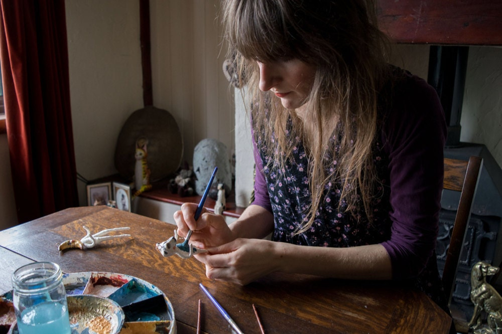 Kayleigh painting a bear ornament at her table