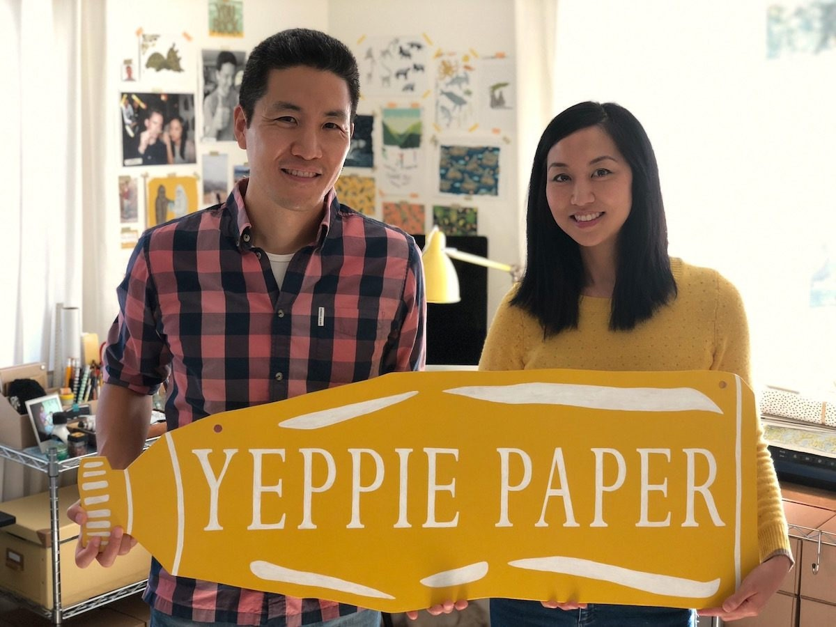 Jen and Jim standing in their studio holding a Yeppie Paper sign