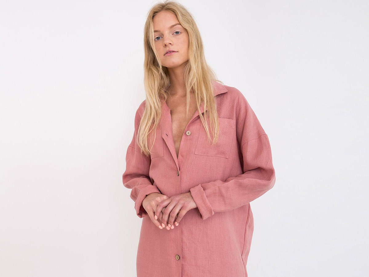 A salmon-colored button-down linen shirtdress on a model.