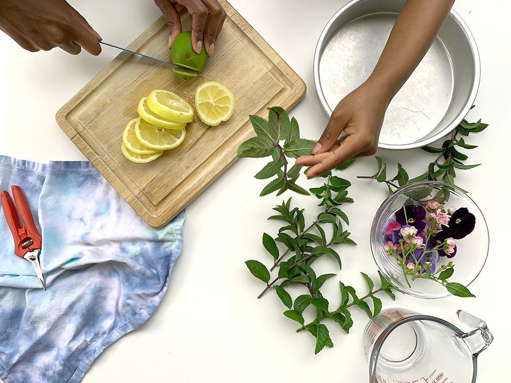Aravis slices lemons and limes while her niece pulls mint leaves off their stems.