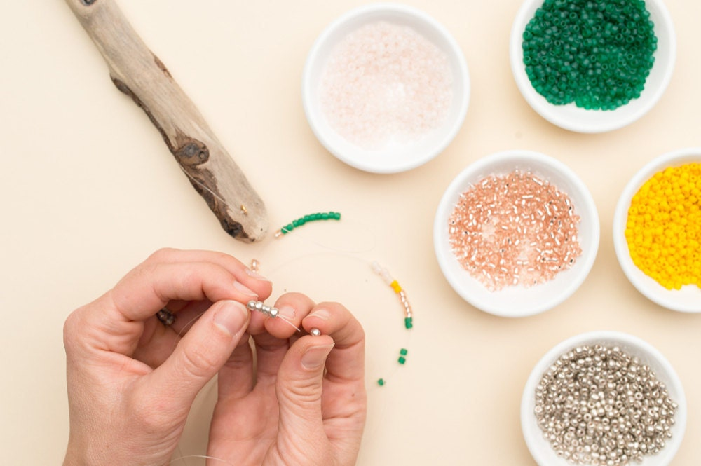 Stringing colorful seed beads onto the fishing line