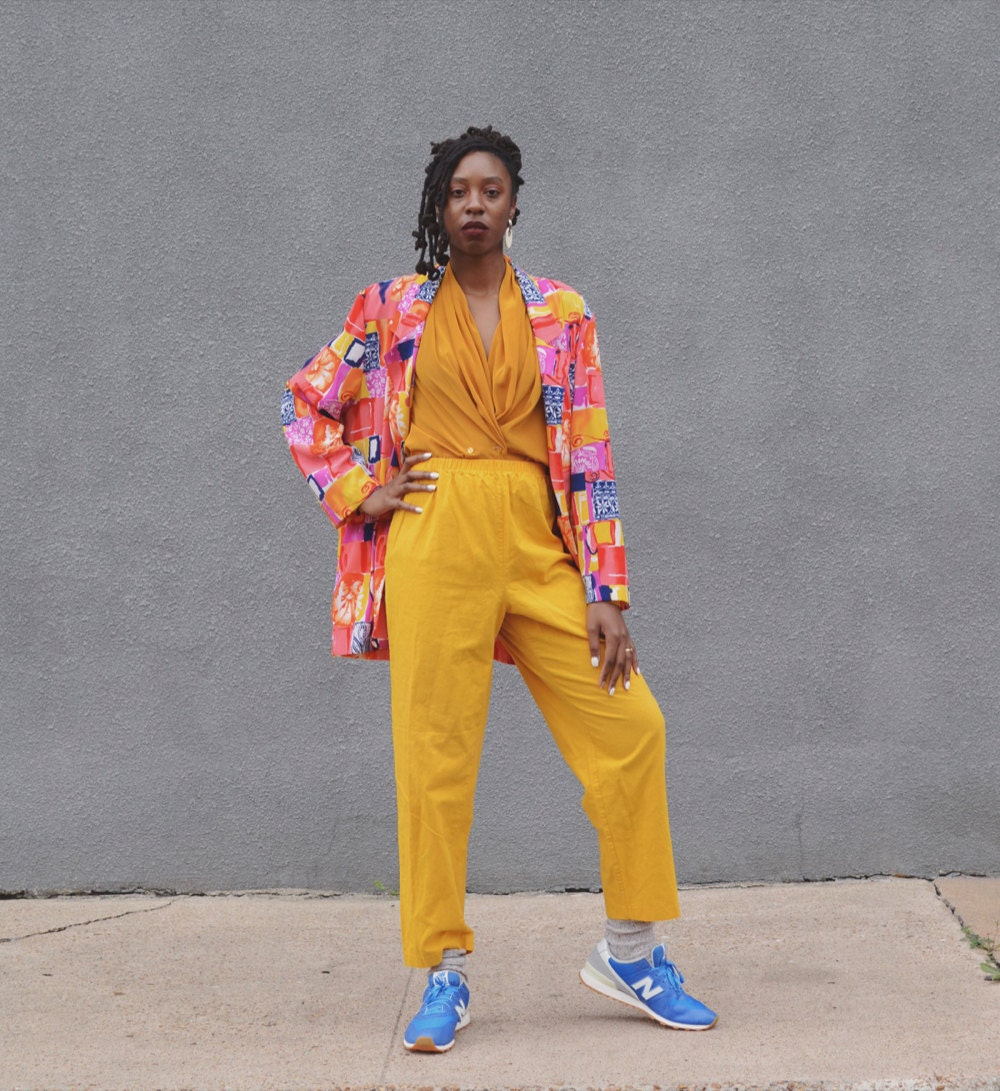 Rachelle models a colorful vintage outfit (including matching yellow pants and top, and a neon-multicolored jacket).
