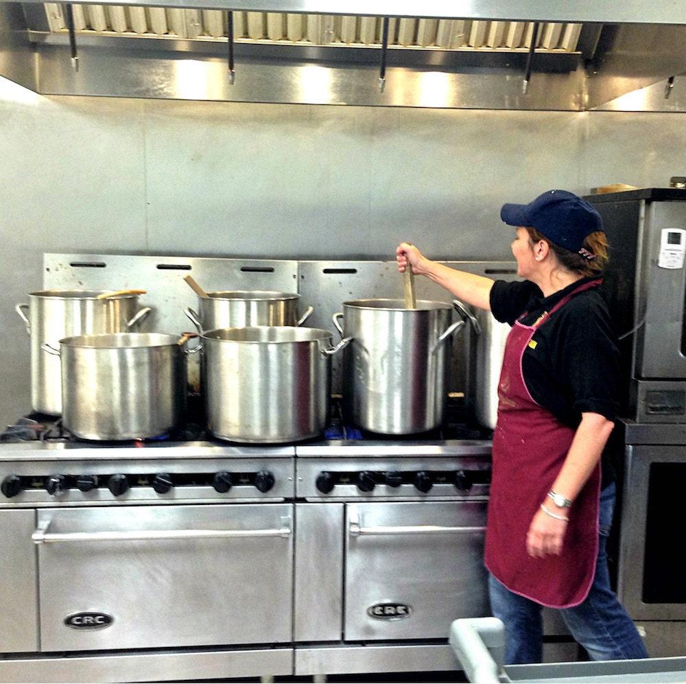 Adriana stirs an oversized pasta pot in her industrial kitchen