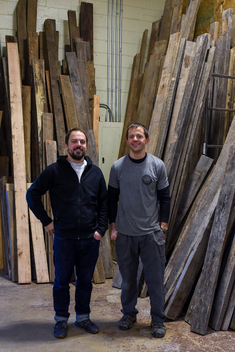 Dan and George standing in front of a collection of reclaimed wood
