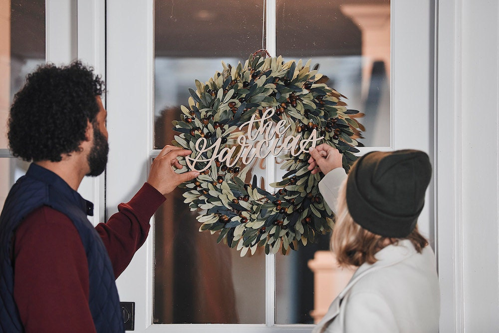 """A couple hangs a faux olive wreath and calligraphy name sign that says """"The Garcias"""" on their front door"""