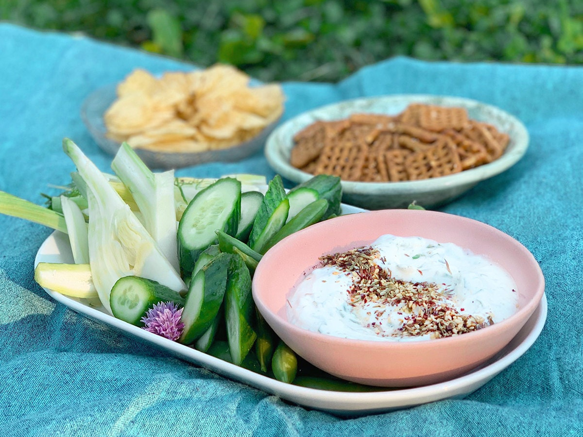 A styled picture of creamy yogurt herb dip on a picnic blanket, with sides