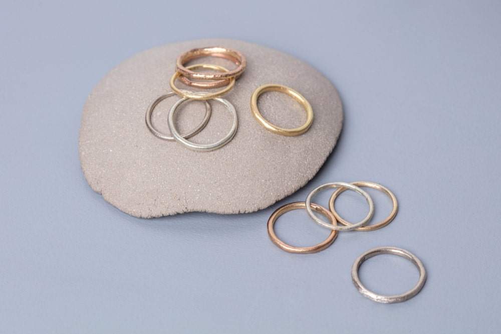 Assorted silver, gold, and rose gold rings on display