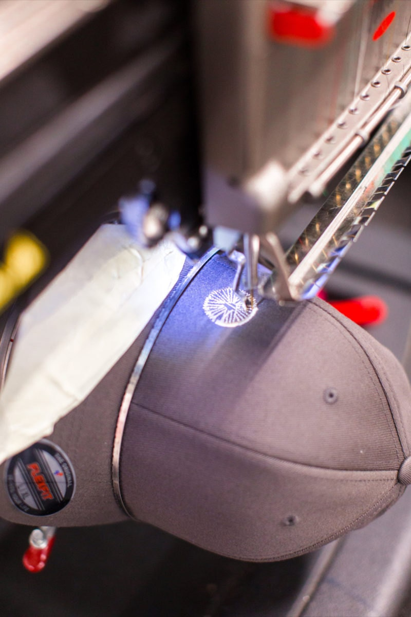 A machine embroidering a bicycle wheel onto a baseball cap.