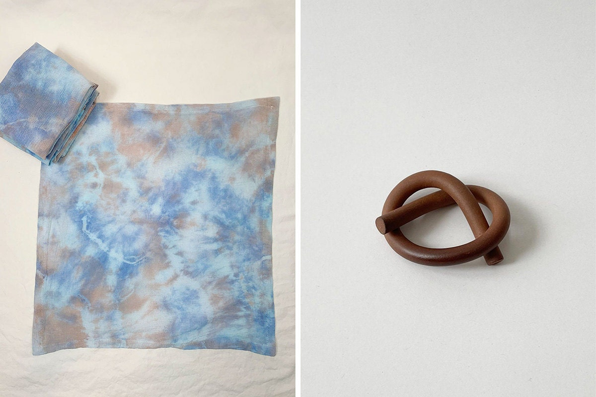 Two images: a blue and grey tie-dye napkin at left and a ceramic napkin holder in the shape of a pretzel at right