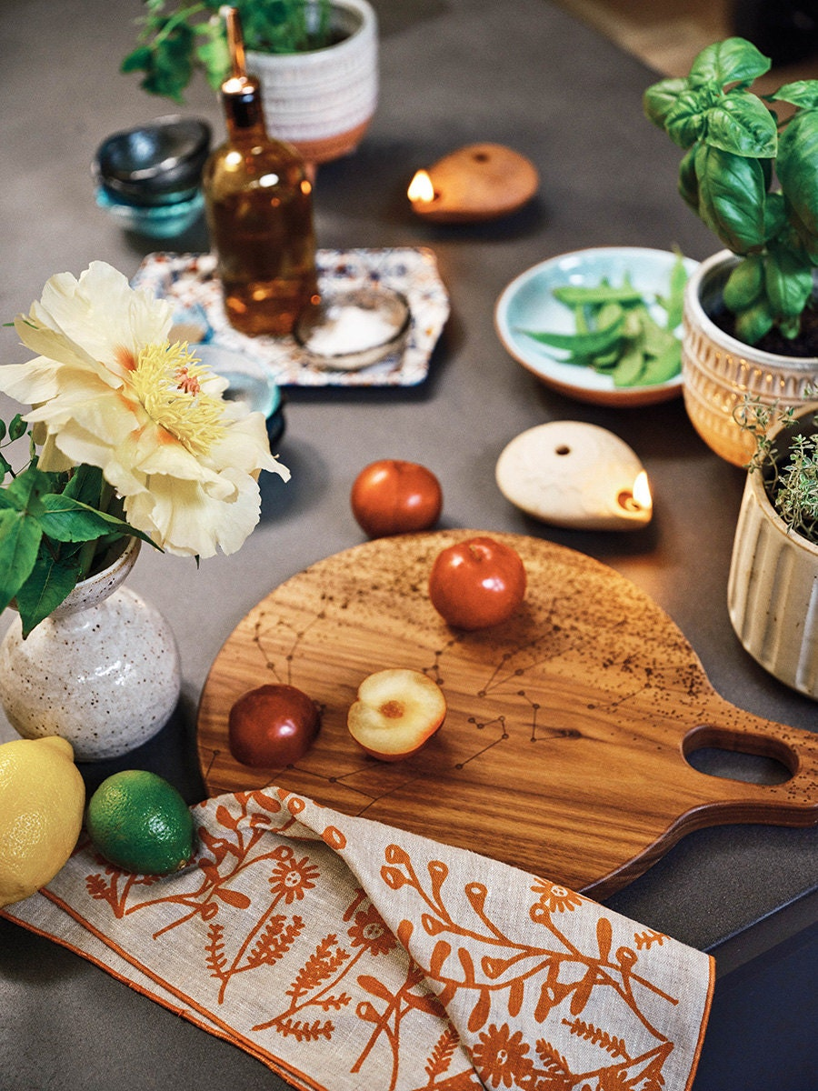 A kitchen counter scene featuring a constellation cutting board with fruit on top