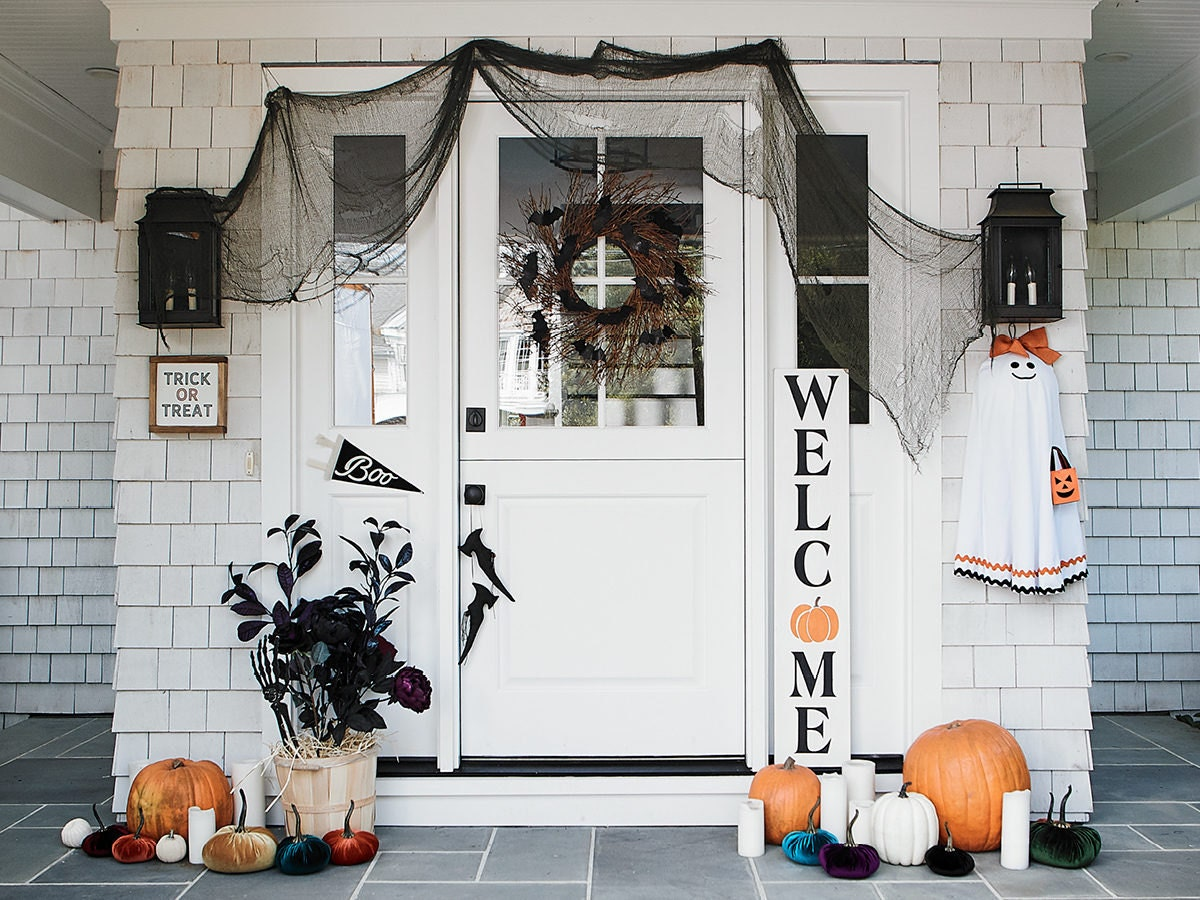 A front porch decorated for Halloween with festive props and signage