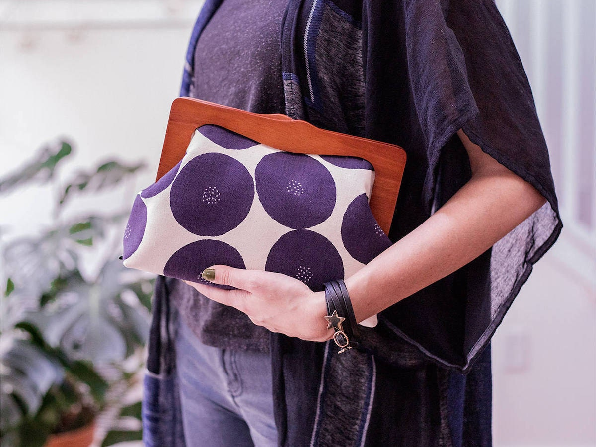 A woman models an oversized fabric clutch with a wooden handle from Boejack Design
