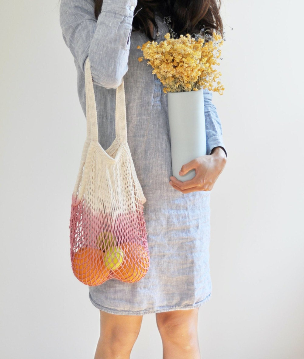 A woman carrying fresh produce in a pink dip-dyed netted market tote.