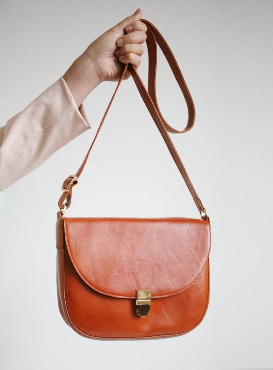 A crossbody buckle bag from Alex Bender in cognac