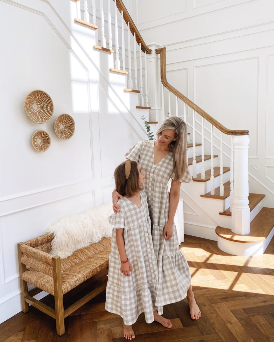 Kristine and her daughter, wearing matching linen dresses, embrace.