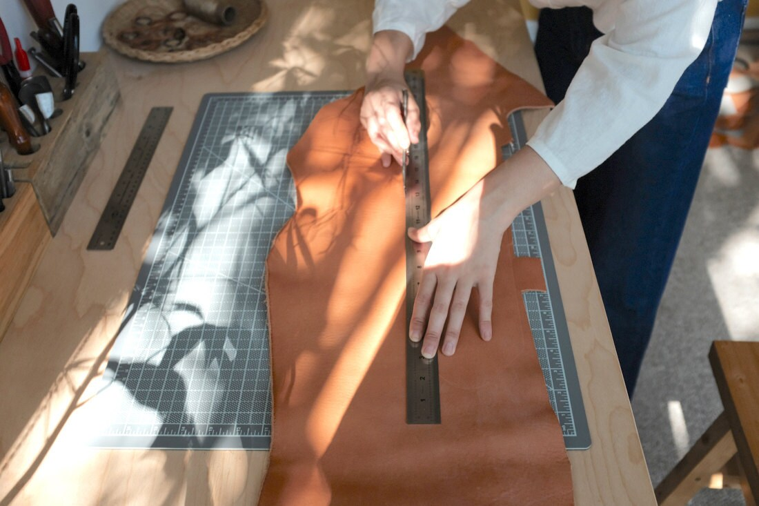 Quynh measures a length of leather, marking where to cut
