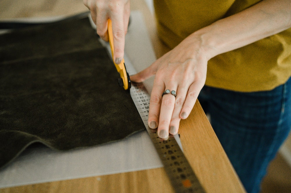 Eda cutting leather fabric for one of her totes