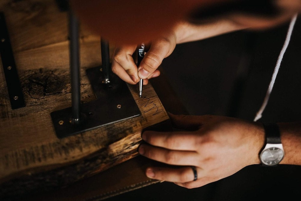 A CBYMCREATIVE woodworking puts a finishing touch on a piece