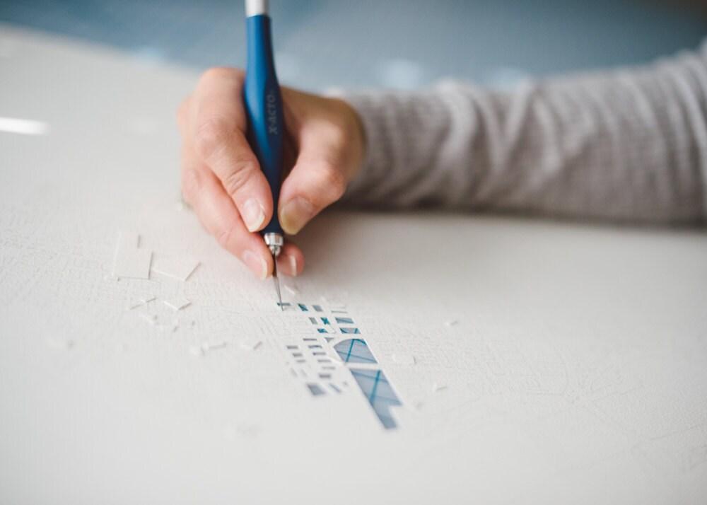 Close-up on Karen cutting a paper-cup map