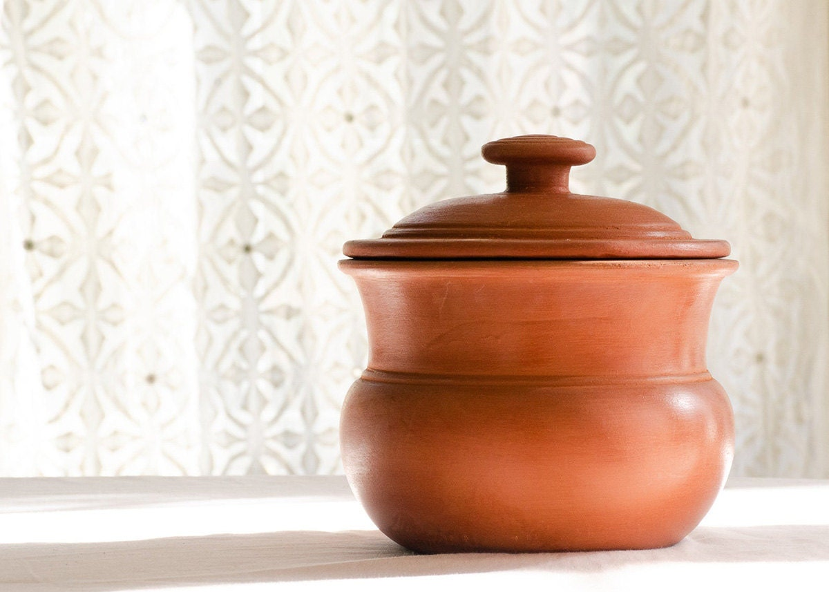 A terracotta curry pot with a white patterned curtain in the background
