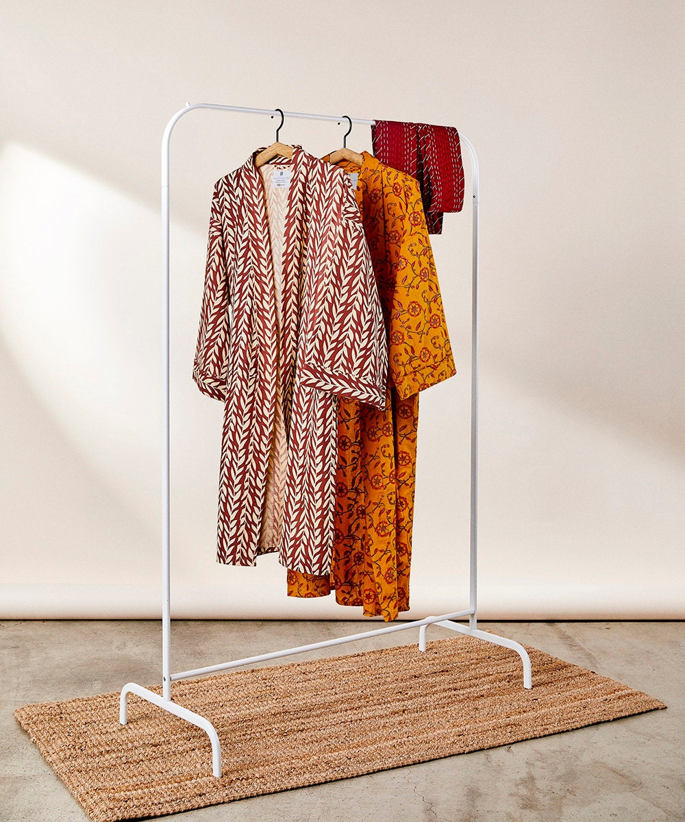 Colorful caftans on a clothing rack.